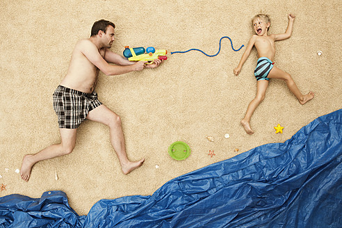 Germany, Father and son playing with water guns at beach - BAEF000291