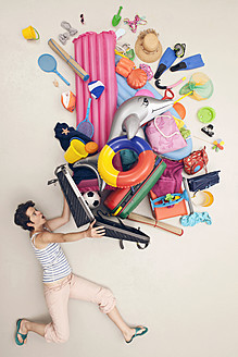 Germany, Artificial scene with woman opening baggage full of beach toys - BAEF000320