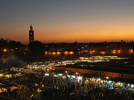 Morocco, Marrakesh, People at Djemaa el Fna square with Koutoubia Mosque at night - BSCF000060