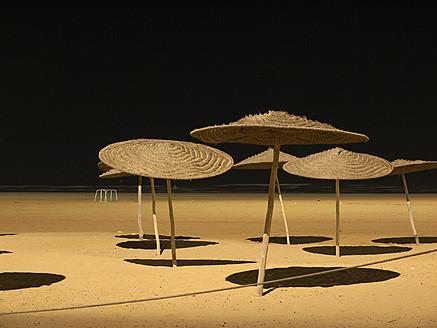 Morocco, Essaouira, Sunshades on beach at night - BSCF000084