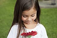 Germany, Bavaria, Huglfing, Girl with flower in garden, smiling - RIMF000018