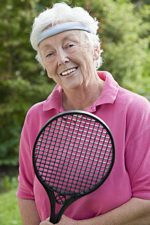 Germany, Bavaria, Huglfing, Senior woman holding badminton racket, smiling, portrait - RIMF000012
