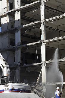 Germany, Berlin, Man watering on demolished house - JM000060