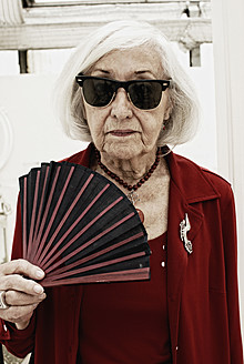 Germany, Bavaria, Munich, Senior woman with folding fan, portrait - DKF000195