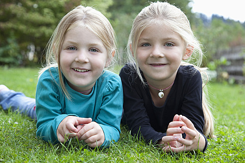 Germany, Bavaria, Huglfing, Girls lying on grass in garden, smiling, portrait - RIMF000031