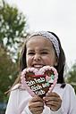Germany, Bavaria, Huglfing, Girl holding gingerbread heart in garden, smiling, portrait - RIMF000034