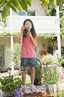 Germany, Bavaria, Girl blowing soap bubbles in garden - WESTF017698