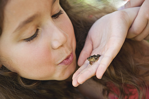 Germany, Bavaria, Girl looking at little frog on human hand - WESTF017713
