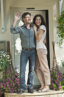 Germany, Bavaria, Couple at entrance of house, smiling - WESTF017757