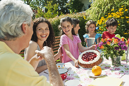 Germany, Bavaria, Family having coffee and cake in garden, smiling - WESTF017786