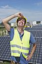 Germany, Munich, Technician in solar plant, smiling - WESTF017839