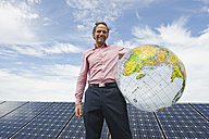 Germany, Munich, Mature man holding globe in solar plant, smiling, portrait - WESTF017866