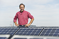 Germany, Munich, Mature man standing in solar plant, smiling, portrait - WESTF017869