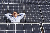 Germany, Munich, Mature man resting on panel in solar plant, smiling - WESTF017872