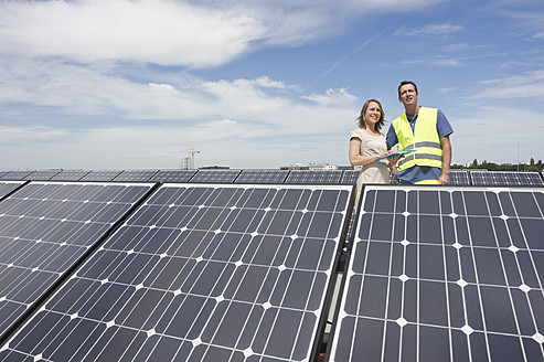 Germany, Munich, Engineers standing in solar plant, smiling - WESTF017884