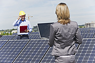 Germany, Munich, Engineers with laptop and discussing in solar plant - WESTF017887