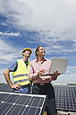 Germany, Munich, Engineers with laptop in solar plant - WESTF017896