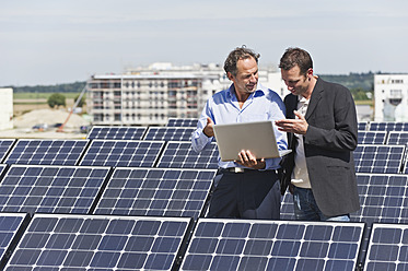 Germany, Munich, Engineer and man discussing in solar plant - WESTF017899