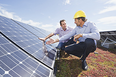 Germany, Munich, Man discussing with engineer in solar plant - WESTF017905