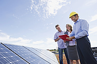 Germany, Munich, Engineer with man and woman in solar plant, smiling - WESTF017908