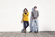 Germany, Bavaria, Munich, Young couple standing against wall - RBF000748