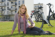 Germany, Bavaria, Teenage girl sitting in grass by bicycle, portrait - RNF000690