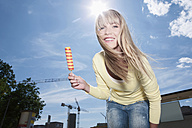Germany, Cologne, Young woman holding ice cream, smiling, portrait - WESTF017947