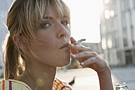 Germany, Cologne, Young woman smoking, portrait - WESTF017959