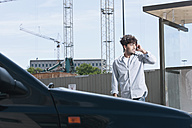 Germany, Cologne, Young man using cell phone - WESTF017974