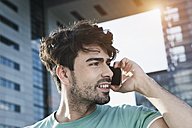 Germany, Cologne, Young man using cell phone, smiling - WESTF017977