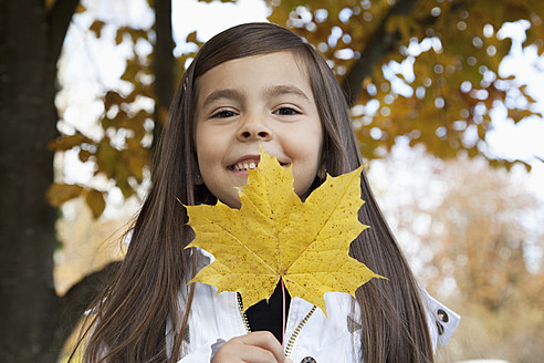 Germany, Huglfing, Girl holding leaf, smiling, portrait - RIMF000067