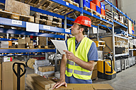 Germany, Bavaria, Munich, Manual worker with clipboard in warehouse - WESTF018032