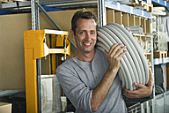 Germany, Bavaria, Munich, Manual worker carrying plastic hose, smiling, portrait - WESTF018053