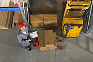 Germany, Bavaria, Munich, Manual worker with clipboard in warehouse - WESTF018062