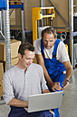 Germany, Bavaria, Munich, Manual workers using laptop in warehouse - WESTF018074
