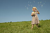 Germany, Bavaria, Girl blowing soap bubbles - RNF000736