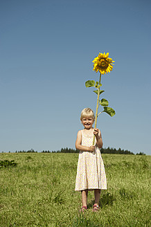 Germany, Bavaria, Girl standing in grass with sunflower - RNF000740