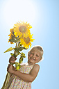 Germany, Bavaria, Girl with sunflower, smiling, portrait - RNF000743