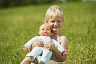 Germany, Bavaria, Girl with baby doll in grass, smiling, portrait - RNF000746