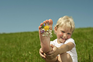 Germany,  Bavaria, Girl playing with flowers between toes on grass, smiling, portrait - RNF000752