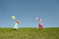Germany, Bavaria, Girls walking in grass with balloons - RNF000755