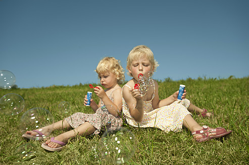 Germany, Bavaria, Girls sitting in grass and blowing bubbles - RNF000758