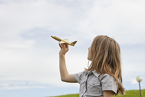 Germany, Bavaria, Girl playing with model airplane in park - SKF000558