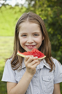 Germany, Bavaria, Girl eating watermelon in park, smiling, portrait - SKF000561