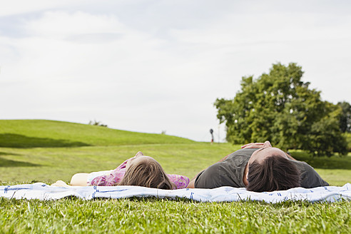 Germany, Bavaria, Father and daughter relaxing in grass - SKF000582
