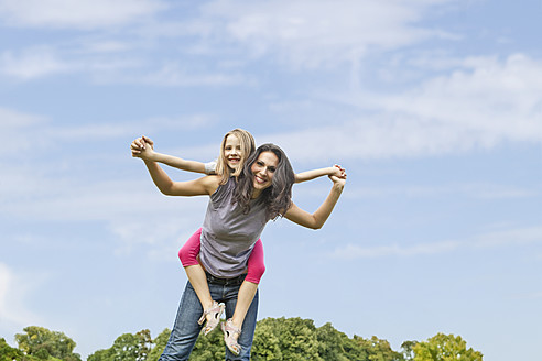 Germany, Bavaria, Mother giving piggy back ride to daughter in park, smiling, portrait - SKF000588