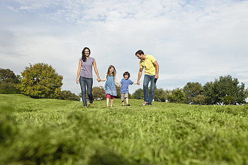 Germany, Bavaria, Family walking in grass at park - SKF000621