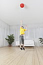 Germany, Munich, Boy jumping for balloon - SKF000627
