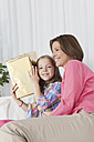 Germany, Munich, Mother and daughter with gift, smiling - SKF000645