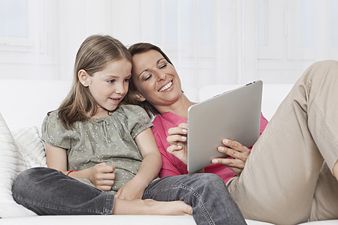 Germany, Munich, Mother and daughter using digital tablet, smiling - SKF000651